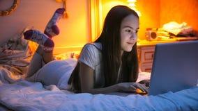 Retrato de la muchacha sonriente hermosa que miente en cama y que usa el ordenador portátil Imagen de archivo