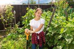 Retrato de la muchacha sonriente hermosa que presenta en el jardín con la pala Foto de archivo