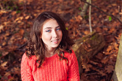 Retrato de la muchacha sonriente joven en el bosque del otoño Fotos de archivo libres de regalías