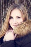Retrato de la muchacha sonriente joven en parque del invierno Foto de archivo