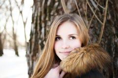 Retrato de la muchacha sonriente joven en parque del invierno Fotos de archivo libres de regalías