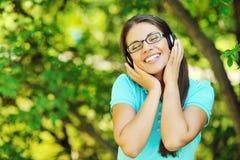 Retrato de la muchacha sonriente joven que escucha la música con el auricular Fotos de archivo libres de regalías