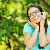 Retrato de la muchacha sonriente joven que escucha la música con el auricular Fotografía de archivo libre de regalías