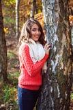 Retrato de la muchacha sonriente joven que se coloca cerca del árbol Fotografía de archivo