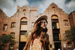 Retrato de la muchacha sonriente linda en gafas de sol con los edificios de la ciudad en el fondo foto de archivo libre de regalías