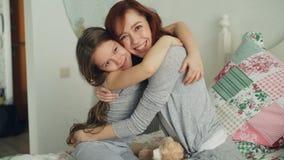 Retrato de la muchacha sonriente linda que abraza a su madre feliz que mira la cámara junto mientras que se sienta en cama en bri almacen de metraje de vídeo