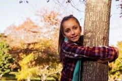 Retrato de la muchacha sonriente que abraza el árbol Fotos de archivo libres de regalías