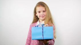 Retrato de la muchacha sonriente que da el regalo por una mano concepto de la enhorabuena metrajes