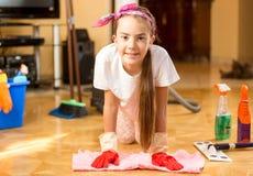 Retrato de la muchacha sonriente que limpia el piso de madera con el trapo Fotografía de archivo