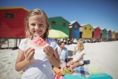 Retrato de la muchacha sonriente que sostiene la sandía con los padres en fondo Fotografía de archivo