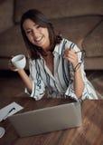 Retrato de la muchacha sonriente que usa el ordenador portátil y bebiendo el coff foto de archivo