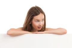 Retrato de la muchacha sorprendida detrás del cartel Imagen de archivo libre de regalías