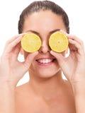 Retrato de la muchacha, sosteniendo naranjas sobre ojos Fotografía de archivo