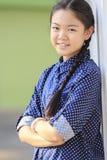 Retrato de la muchacha tailandesa de los años 12s que lleva la camisa azul que se destaca Fotos de archivo