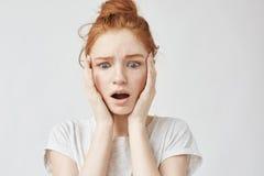 Retrato de la muchacha trastornada sorprendida del pelirrojo con las manos en mejillas, descubriendo algo Fondo blanco, espacio d Fotos de archivo