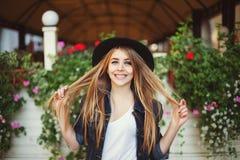 Retrato de la muchacha traviesa linda que juega con su pelo Fondo colorido Foto de archivo libre de regalías