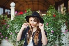 Retrato de la muchacha traviesa linda que juega con su pelo Fondo colorido Imagen de archivo