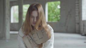 Retrato de la muchacha triste con el pelo rojo largo en un cuarto vacío polvoriento grande en la sensación constructiva abandonad almacen de metraje de vídeo