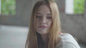 Retrato de la muchacha triste con el pelo rojo largo en un cuarto vacío polvoriento grande en la sensación constructiva abandonad almacen de video
