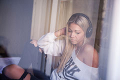 Retrato de la muchacha triste hermosa con los auriculares que escucha la música rock Imágenes de archivo libres de regalías