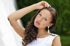 Retrato de la muchacha triste hermosa en el vestido blanco que se inclina en el wal fotos de archivo libres de regalías