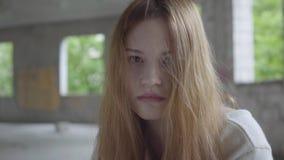 Retrato de la muchacha triste joven caucásica que se sienta en un edificio abandonado que tiene ayuda de fractura o que espera de almacen de metraje de vídeo