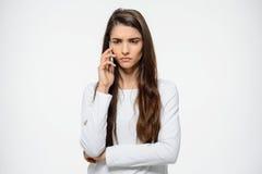 Retrato de la muchacha triste joven que habla en su teléfono sobre el fondo blanco que es trastornado Imagenes de archivo