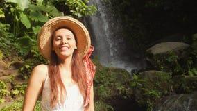 Retrato de la muchacha turística sonriente joven de la raza mixta en el vestido y Straw Hat blancos con sorprender la cascada sal almacen de metraje de vídeo