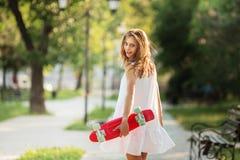 Retrato de la muchacha urbana preciosa en el vestido blanco con un skatebo rosado Imagen de archivo