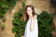 Retrato de la muchacha urbana preciosa en vestido blanco corto en la calle Imagen de archivo