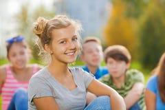 Retrato de la muchacha y de amigos sonrientes en fondo Imagen de archivo