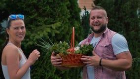 Retrato de la muchacha y del individuo de risa con la cesta de verduras al aire libre almacen de video