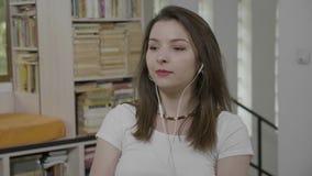 Retrato de la mujer adolescente sonriente que mira el escuchar lejos que sueña despierto y feliz el audiolibro en su sitio - almacen de video