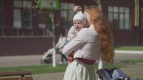 Retrato de la mujer adorable que detiene al bebé en brazos y que sonríe en el primer de la yarda La señora que disfruta del día s almacen de metraje de vídeo