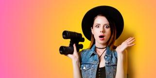 Retrato de la mujer adulta joven en sombrero con binocular Imágenes de archivo libres de regalías