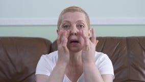 Retrato de la mujer adulta que mira la c?mara como el espejo y la preocupaci?n sobre su cara con las arrugas y edad Se?ora almacen de video