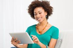 Mujer africana que mira la tableta de Digitaces Foto de archivo