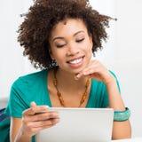 Mujer africana que mira la tableta de Digitaces Fotos de archivo libres de regalías
