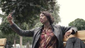 Retrato de la mujer africana joven elegante que toma el selfie con su teléfono elegante almacen de video