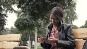 Retrato de la mujer africana joven hermosa que sonríe mientras que se sienta afuera en un banco que sostiene el teléfono móvil de almacen de metraje de vídeo