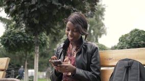 Retrato de la mujer africana joven hermosa que sonríe mientras que se sienta afuera en un banco que sostiene el teléfono móvil de almacen de video