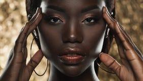 Retrato de la mujer africana joven sensual contra fondo de oro imagenes de archivo