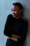 Retrato de la mujer africana joven sonriente con los labios violetas brillantes que miran lejos el fondo gris Imágenes de archivo libres de regalías