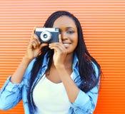 Retrato de la mujer africana sonriente feliz con la cámara vieja del vintage sobre rojo Fotografía de archivo