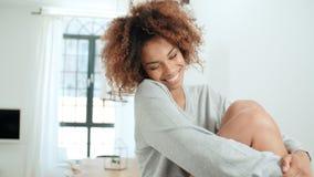 Retrato de la mujer afroamericana alegre que se sienta en una tabla de cocina en casa Fotos de archivo