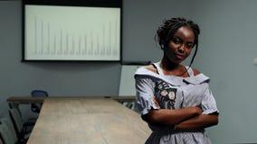 Retrato de la mujer afroamericana del hombre de negocios que se coloca en oficina delante de una tabla grande y gráficos en la pa metrajes