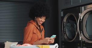 Retrato de la mujer afroamericana feliz joven con el smartphone que mira en la cámara Lavadero p?blico del autoservicio almacen de video