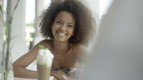 Retrato de la mujer afroamericana joven hermosa con los amigos en el café al aire libre metrajes