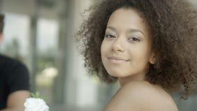 Retrato de la mujer afroamericana joven hermosa con los amigos en el café al aire libre almacen de video