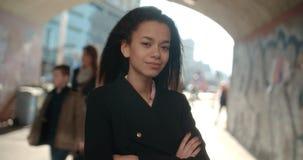 Retrato de la mujer afroamericana joven que mira a una cámara, al aire libre Imagen de archivo